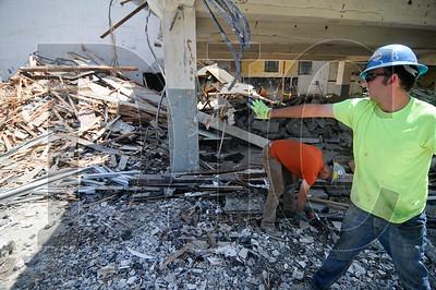 Josh Edinger, right, and Jeff Wagner sort demolition debris.