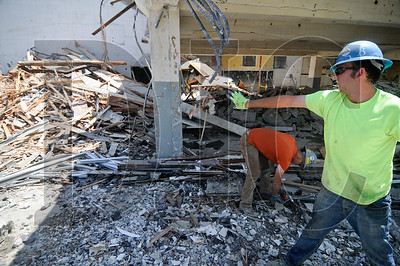 Josh Edinger, right, and Jeff Wagner sort demolition debris.