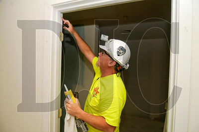 WB Painting & Decorating employee Jeff Skotland fills cracks in a door jamb with caulking.