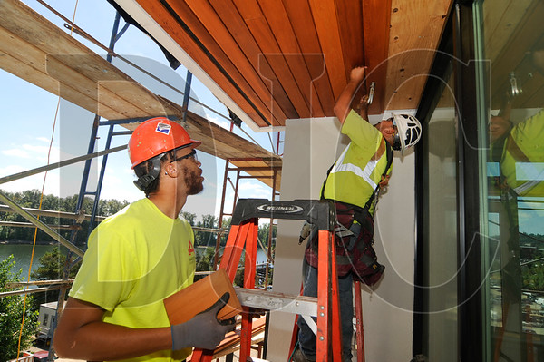 David Smith, left, an apprentice carpenter with Primo Construction, watches as Neftale Cisneros, a journeyman carpenter with Primo, installs tongue-in-groove cedar on a balcony soffit. (Sam Tenney/DJC)