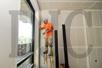 Bernie Rascon, a taper with Anning-Johnson, muds drywall in a ground-floor residential unit.