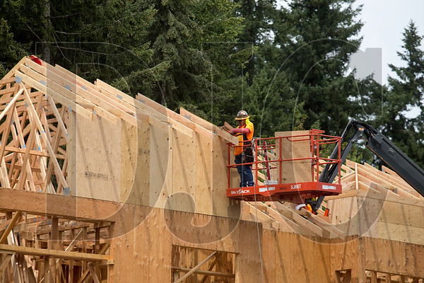 A carpenter with Wood Mechanix builds the roof of the three-story assisted-living building.