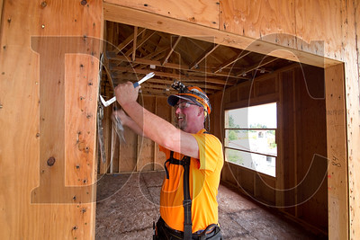 Terry Brooks, a carpenter with Wood Mechanix, removes a tie-down ring.