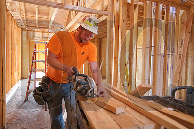 Mike Masloff, a carpenter with Wood Mechanix, cuts material while performing quality control work on the framing of an independent living building.