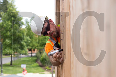 Carpenter Mike Marsh, an employee of Wood Mechanix, marks an exterior wall for nailing patterns and hold-downs in walls.