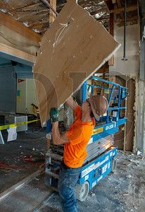 Laborer Alan Holmes of Philco Demolition removes wallboard from cafeteria walls. (Josh Kulla/DJC)