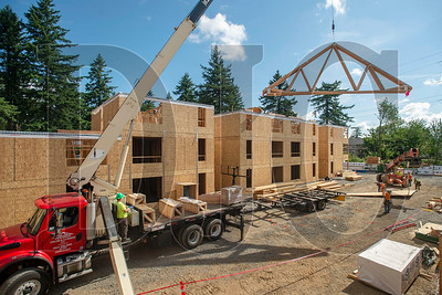 Carpenters with Wood Mechanix fly a truss into place at Archibald Grove, a 37-unit multifamily project under construction in Gresham. (Josh Kulla/DJC)