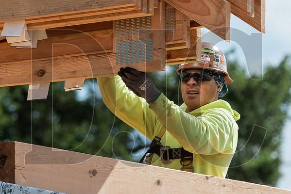 A Wood Mechanix carpenter guides a load of trusses into place. (Josh Kulla/DJC)