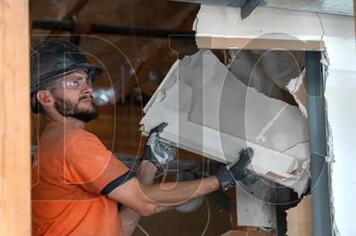 Trevor De La Isla, a laborer with Philco Demolition, demolishes drywall in the cafeteria of Evergreen Middle School in Hillsboro. (Josh Kulla/DJC)