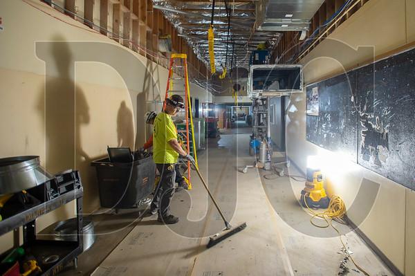 John Tuttle, a journeyman HVAC technician with American Heating, sweeps the floor of debris while installing new ductwork. (Josh Kulla/DJC)