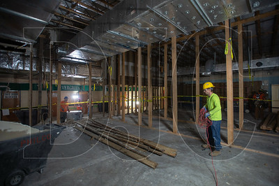 Josh Bradley, a laborer with Philco Demolition, wraps up electrical cord while working on the demolition of the cafeteria and adjacent classrooms. (Josh Kulla/DJC)