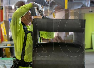 Jeff Sullins, a journeyman HVAC technician and employee of American Heating, repairs a piece of ductwork. (Josh Kulla/DJC)
