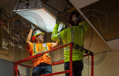 Alfredo Uribe, left, and Abel Tobar, both journeyman carpenters with Local 271 and employees of Ward Henshaw Construction, remove a light fixture from an Evergreen Middle School classroom ceiling before installing temporary plywood bracing. (Josh Kulla/DJC)