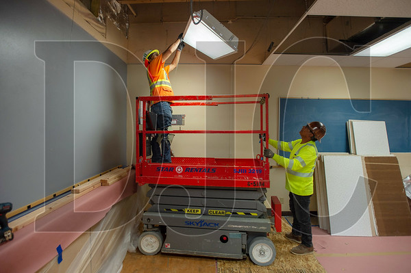 Alfredo Uribe, left, and Abel Tobar, both journeyman carpenters with Local 271 and employees of Ward Henshaw Construction, remove a light fixture from a classroom ceiling before installing temporary plywood bracing. (Josh Kulla/DJC)