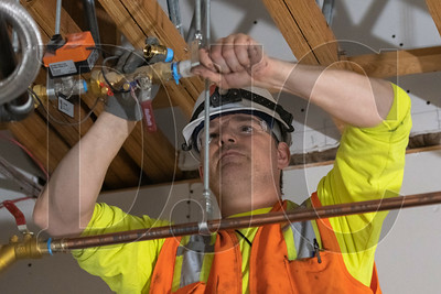 Arrow Nail, a journeyman plumber with American Heating Inc., tightens a connection on a section of hydronic piping. (Josh Kulla/DJC)