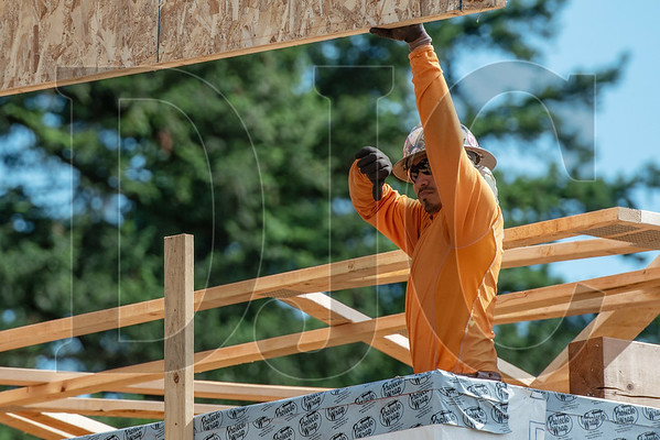 Wood Mechanix carpenter and crew foreman Pedro Guillen-Pacheco directs a crane operator flying a load of trusses at the Archibald Grove Apartments in Gresham. (Josh Kulla/DJC)