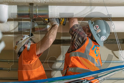 Journeyman electricians Bill Elliott, and Paul Deemie, both employees of IES Commercial and Industrial, hang brackets for electrical conduit. (Josh Kulla/DJC)