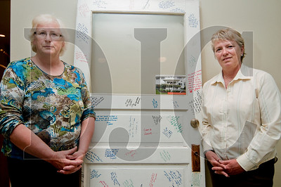 Dougy Center Program Director Joan Schweizer Hoff, left, and executive director Donna Schuurman stand in front of a door that was used in the center's former main building in Southeast Portland.  The door was signed by Dougy Center clients at a goodbye ceremony for the building, which was destroyed by fire in 2009.