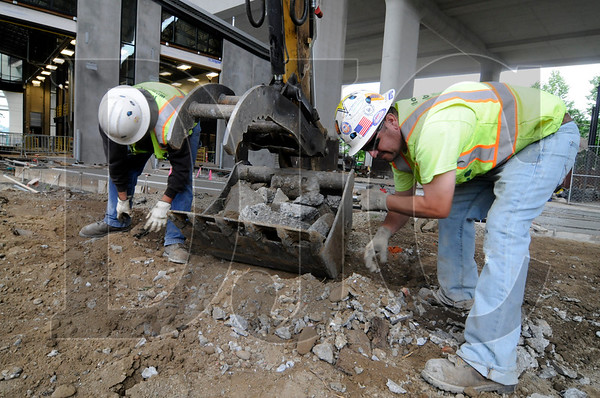 Stacy and Witbeck employees Arnold Espinoza, left, a laborer and member of Laborers Local 320, and Steve Morrison, a heavy equipment operator and foreman and member of IOUE Local 701, load small pieces of concrete into an excavator at the site of a Tri-Met streetcar service facility in Northwest Portland on Friday.