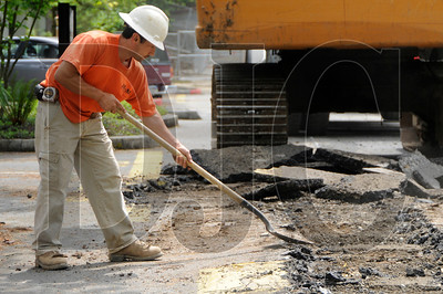 M&M Construction employee Juan Gomez shovels asphalt while digging for storm and sewer lines at the site of a new dormitory construction at Lewis & Clark College on Monday.
