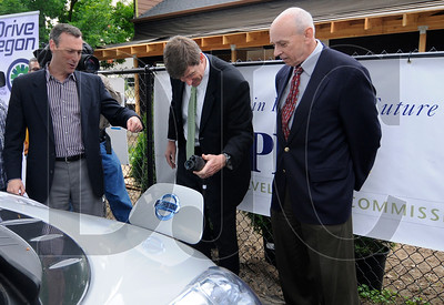 Multnomah County Chair Jeff Cogen, left, and Bonneville Power Administration Energy Efficiency Vice President Mike Weedall, right, watch as Portland Development Commission Executive Director Patrick Quinton unplugs a charger from an electric vehicle during an opening ceremony for a public EV charging station in Northeast Portland on Wednesday.