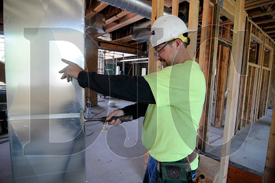 Kirk Linville, of PACE Heating & Air, prepares ducts for installation at the site of the Sunnyside Village Public Library in Happy Valley on Thursday.