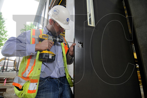 Marc-Daniel Domond, a project manager with Colas Construction, installs a lock on a door at the site of a Tri-Met streetcar service facility in Northwest Portland on Friday.