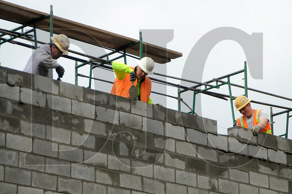 From left, Doug Marti, Dan Hatch, and Brent Bedortha, masons with KPMC, build a wall at the Lake Grove project in Lake Oswego on Thursday.  Beam Development is pursuing Earth Advantage Commercial certification on the project as a less expensive alternative to LEED certification.