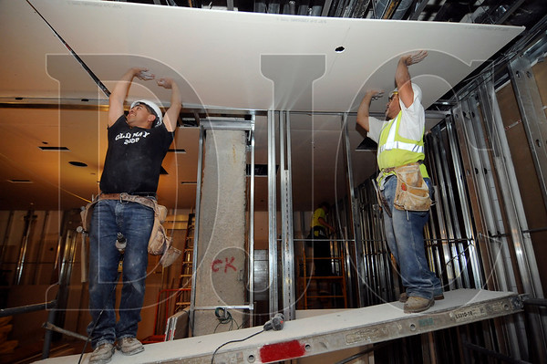 Felipe Rocha, left, and Hilario Hibarra of Columbia Drywall Systems fasten drywall on the ceiling of the Gap store at Pioneer Place on May 26.  General contractor Swinerton Builders is in the second of a two-phase remodel of the store, with expected completion later this month.