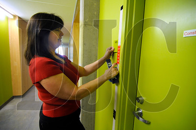 Linda Mack, of Fox Architectural Signs, installs a room number one of the 130 apartments at the Bud Clark Commons in Northwest Portland on Wednesday.  The public opening of the $46.9 million project is today, and residents will begin moving in next week.