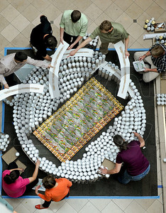 Members of a team comprised of employees of R&H Construction, LRS Architects, and New Seasons Market build a replica of Autzen Stadium Monday during the annual Canstruction event at Pioneer Place Mall in downtown Portland. Nine teams are competing to build structures almost entirely from canned foods in the Society for Design Administration-sponsored event, which collects food and donations for the Oregon Food Bank. Various juried awards will be given out during a banquet Tuesday evening, and the designs will be on display at the mall through June 10.