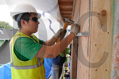 Miguel Javier, a framer with Rothchild Construction, installs a flat strap on the exterior of the Otesha Place Apartments in Northeast Portland June 1.