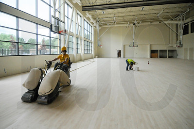 Crews finish the floor of the building's regulation-sized basketball court.