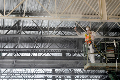 Paint is applied to the rafters in the complex's indoor pool area, which features a recreational pool with a water slide, a lap pool, and an indoor/outdoor hot tub.