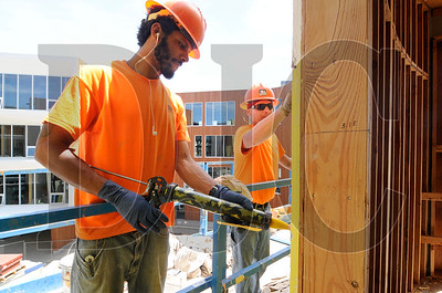 Cy Robertson, left, and Ricky Knowles, both carpenters with R&H Construction, apply liquid flashing to the building's exterior.