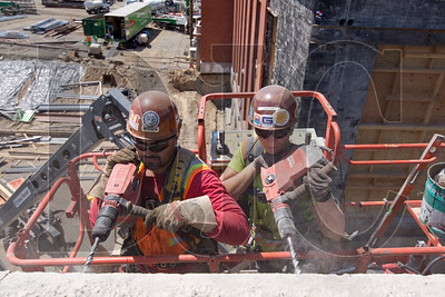 Christian Garcia, left, a first-term apprentice ironworker, and Jess Ross, a fourth-term apprentice, drill into the existing building's masonry while installing a ledger.