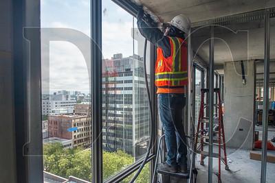 Eder Villasenor, a journeyman glazier with Exterior Designs, places weather sealant in a window frame. (Josh Kulla/DJC)