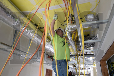 Billy Hudson, an electrician with Bear Electric, prepares to route circuit wiring into a distribution panel at The Springs Living at Lake Oswego. (Sam Tenney/DJC)
