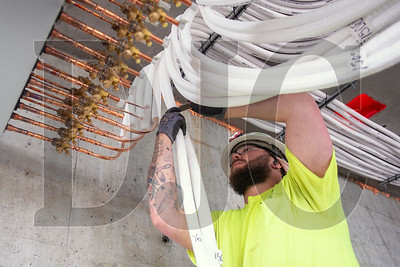 Apprentice pipe fitter Harley Bowlin, a member of Local 290 and an employee of TCM Corp., installs piping for the building's cooling system. (Josh Kulla/DJC)