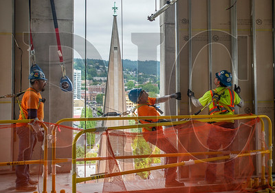 Carpenters with Anning-Johnson set a metal-framed wall section in place at the 15-story Hyatt Centric Portland under construction in downtown Portland. (Josh Kulla/DJC)