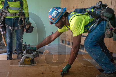 Journeyman carpenter Otha Jones, a member of Local 1503 and crew foreman for Mortenson Construction, cuts a piece of plywood for a temporary wall. (Josh Kulla/DJC)