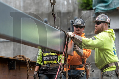 Last month, ironworkers rigged a steel beam on a project at Oregon Health & Science University. Builders could potentially face escalating costs on Chinese steel and alloys as a result of increased tariffs. (Josh Kulla/DJC file)