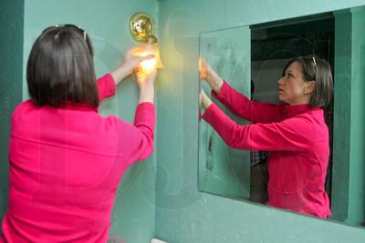 NAWIC member Erin Bullard, an employee of Travelers Bond & Financial Products, installs a compact fluorescent bulb in a bathroom light fixture.