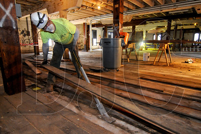 James Baker, a carpenter with Siteworks, removes one of three layers of floorboards on the building's second story.