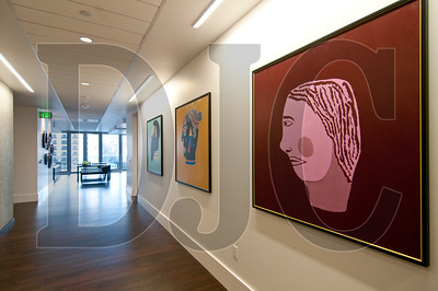 Paintings created by clients of New Avenues for Youth that were used as public art on the perimeter of the job site while the project was under construction are now on display inside the building.