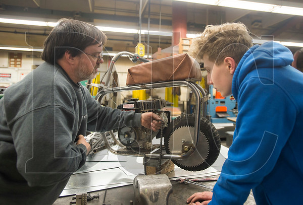 Volunteer Aaron Williams, left, shows Centennial High sophomore Roman Grebelnik the finer points of placing the chain onto the main sprocket of his minibike. (Josh Kulla/DJC)