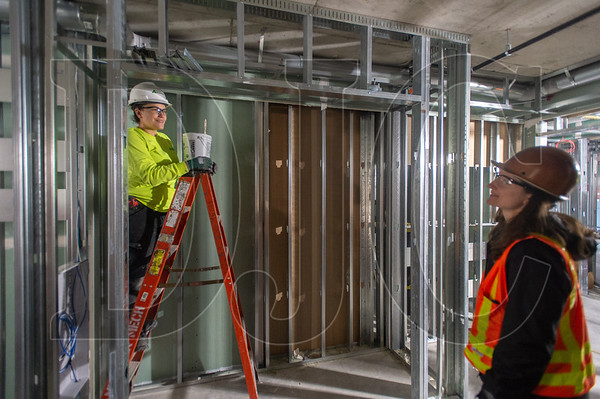 Jamie Vidalez, left, an apprentice HVAC Technician with Andersen Mechanical, talks with Walsh Construction Project Manager Meghan Herteg at the Grand Avenue Apartments project in Northeast Portland. (Josh Kulla/DJC)