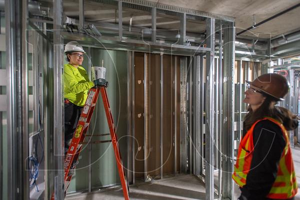 Jamie Vidalez, left, an apprentice HVAC Technician with Andersen Mechanical, talks with Walsh Construction Project Manager Meghan Herteg at the Grand Avenue Apartments project in Northeast Portland. (Josh Kulla/DJC)