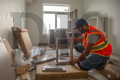 Miguel Villareal, a carpenter with Utah-based contractor CP Build, constructs cabinetry in a residential unit at Koz on 13th. (Josh Kulla/DJC)
