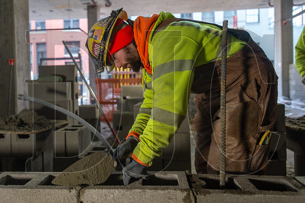 Ben Wall, a journeyman mason with Local 1 and an employee of J&S Masonry, builds a CMU wall on the ground floor of 5 MLK. (Josh Kulla/DJC)